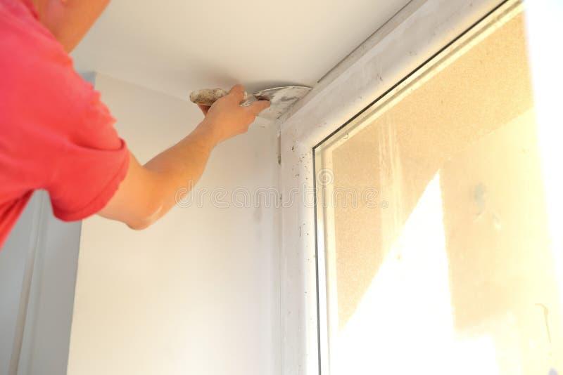 Remplissant et lissant murs utilisant le mastic de gypse photos stock