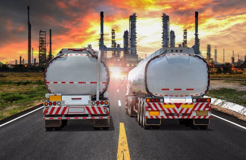 Remplissez de combustible le camion-citerne aspirateur sur la route à l'huile de raffinerie dans le coucher du soleil image stock