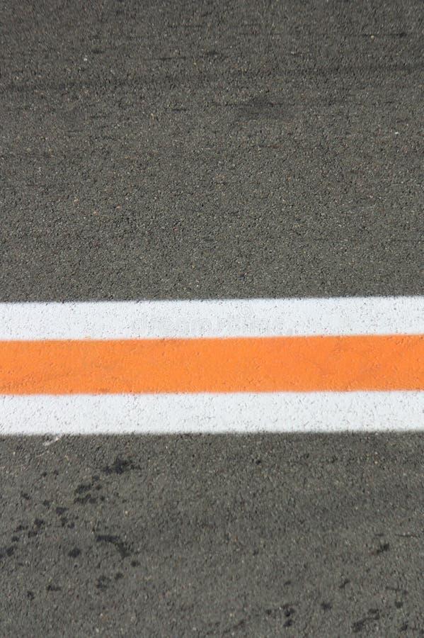 Remsa av vita och orange färger på en grå asfalt arkivfoton