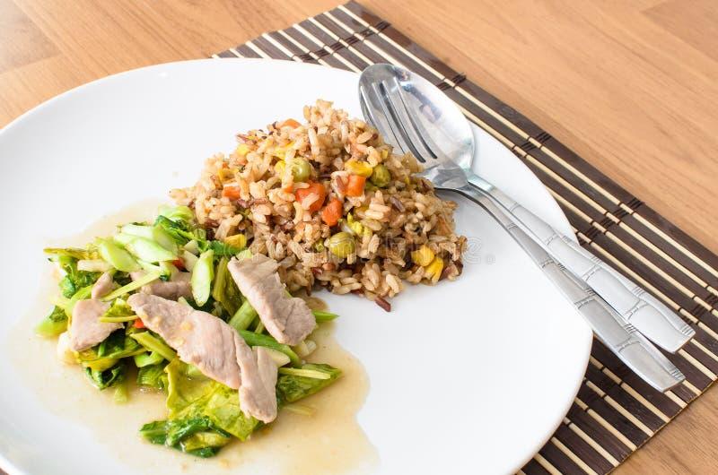 Remuez le Chinois frit de chou frisé avec du porc et le riz coulé de sauce images libres de droits