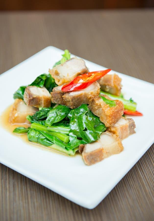 Remuez le chou frisé frit avec du porc croustillant - nourriture chinoise photographie stock