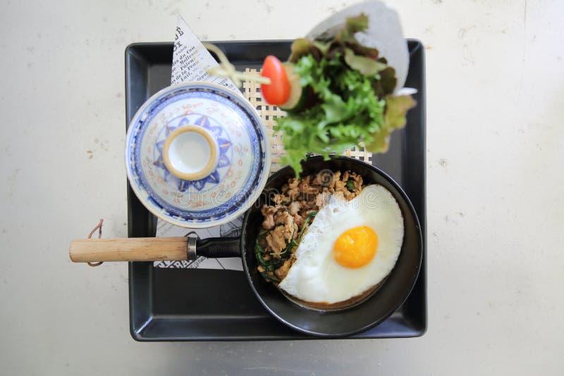 Remuez le porc frit et le basilic servis avec du riz et l'oeuf au plat photographie stock