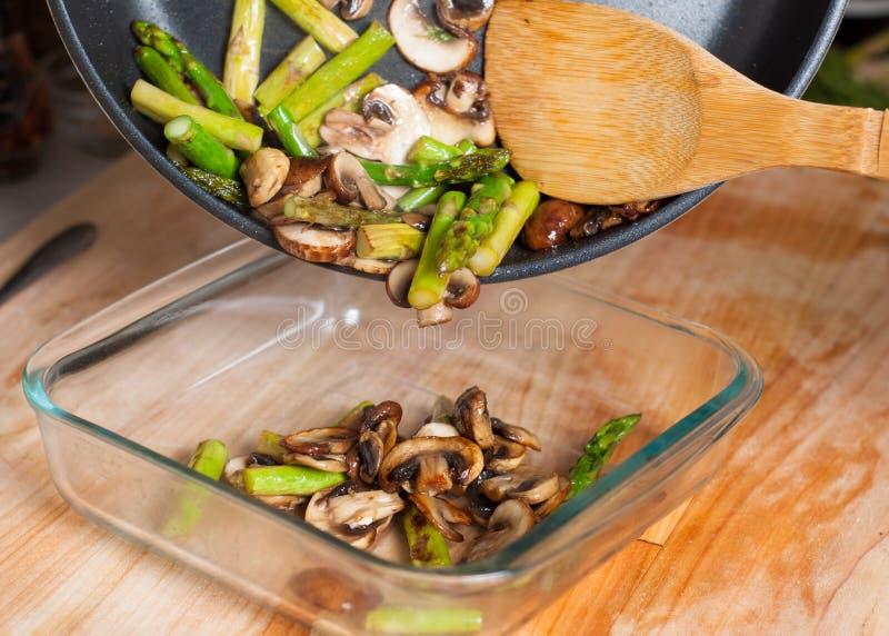 Remuez les champignons frits et l'asperge mettant dans le bakeware image stock