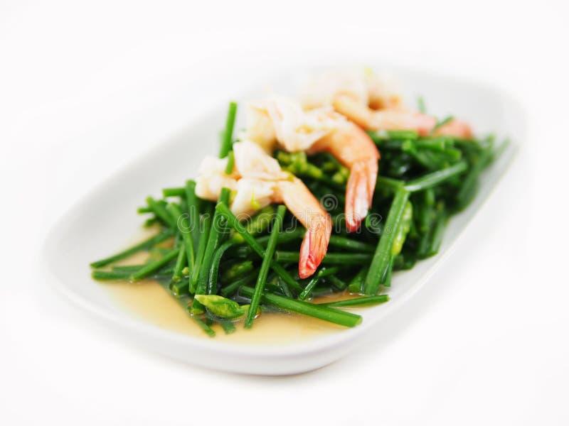 Remuez les crevettes frites avec la ciboulette chinoise dans le plat sur le blanc photos stock