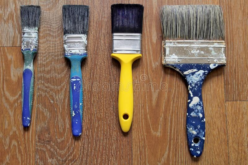 Ren gul målarpensel med smutsiga blåa borstar royaltyfri bild