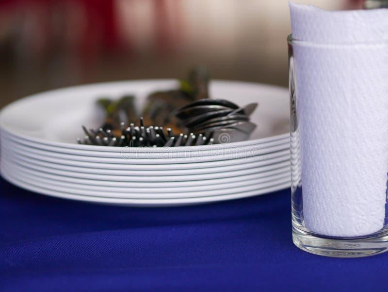 Ren kitchenware, vit melamineplatta, skedar, gafflar och exponeringsglas royaltyfri foto