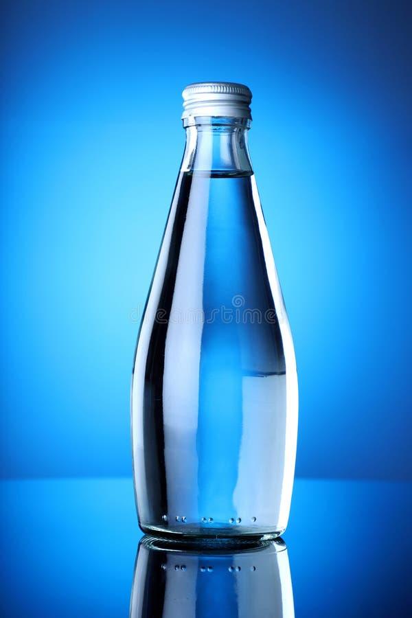 Ren och ren mineralisk dricksvattenflaska med blå bakgrund royaltyfri fotografi