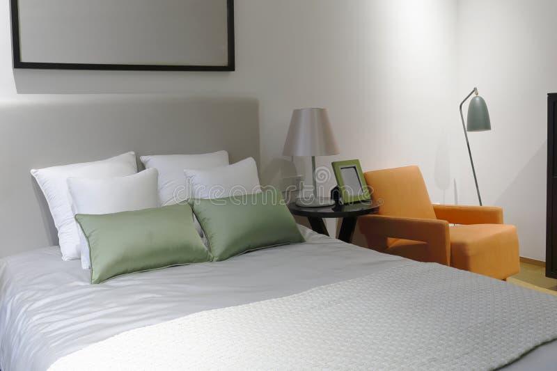 Ren säng och den orange soffan royaltyfri fotografi