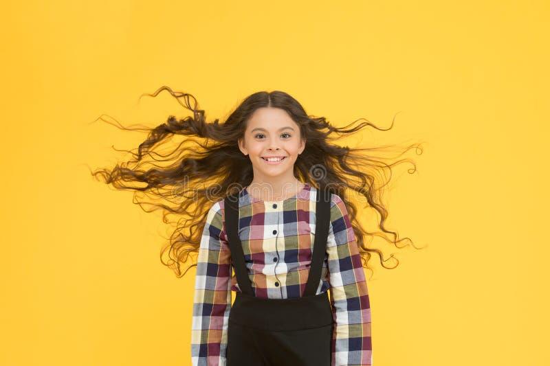 Ren skönhet för ditt hår Glad unge med tungt långt hår Små barn med flygande hårgul bakgrund Skolor arkivfoton