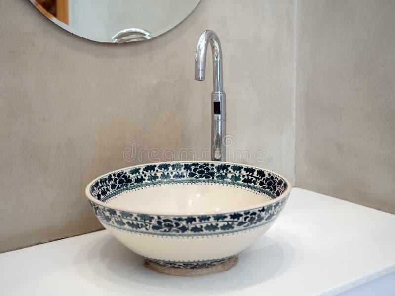 Ren toalettrumstoalett med porslinsbottnar på vit marmorhylla och rund spegel på betongvägg royaltyfri foto