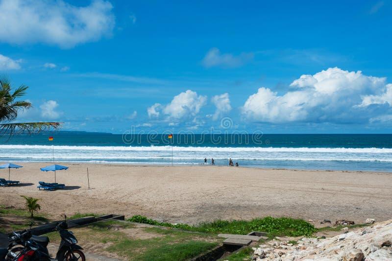 Ren tom tropisk strand med sunbeds under paraplyet och en härlig sikt av det lugna havet under den blåa himlen royaltyfria foton