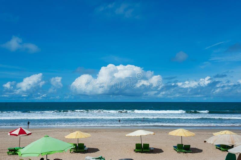 Ren tom tropisk strand med sunbeds under paraplyet och en härlig sikt av det lugna havet under den blåa himlen royaltyfri foto