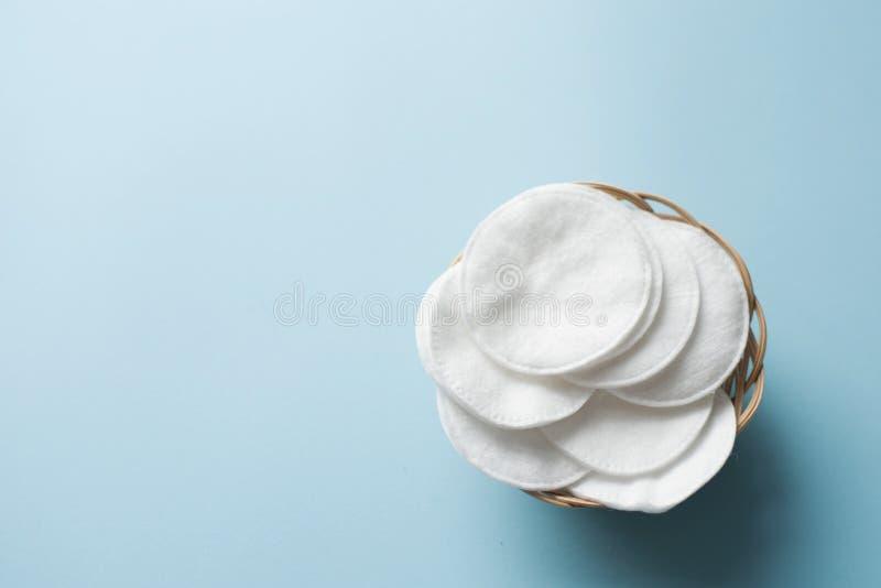 Ren vit bomullsbunt av skivan för skönhetframsidahygien med den selektiva fokusen på blå neutral bakgrund Ren kosmetisk softness royaltyfria foton