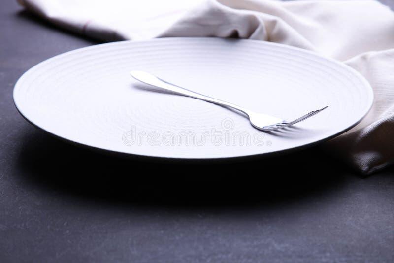 Ren vit platta, gaffel och servett royaltyfri bild
