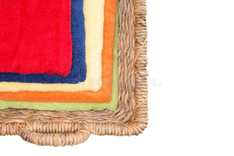 Rena färgrika tvättade handdukar i en vide- korg arkivbilder