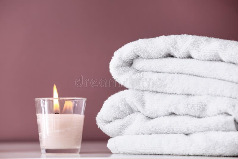 Rena handdukar och brännande stearinljus på hylla i badrum arkivfoton