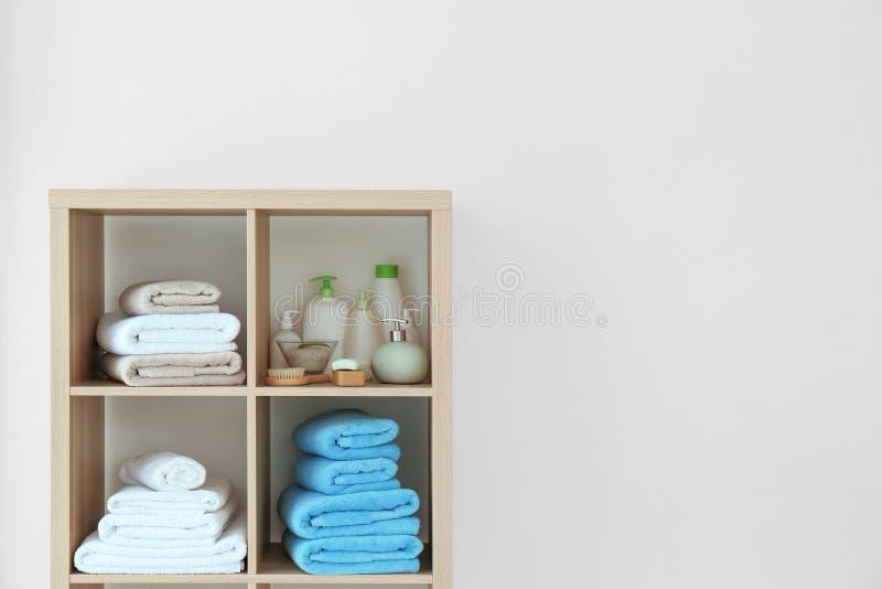 Rena handdukar och skönhetsmedel på hyllor royaltyfria foton