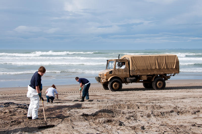 Rena oil spill clean up. Rena ship oil spill clean up on Papamoa beach with New Zealand Army, local volunteers, local moari IWI cleaning beach of oil clumps stock photo
