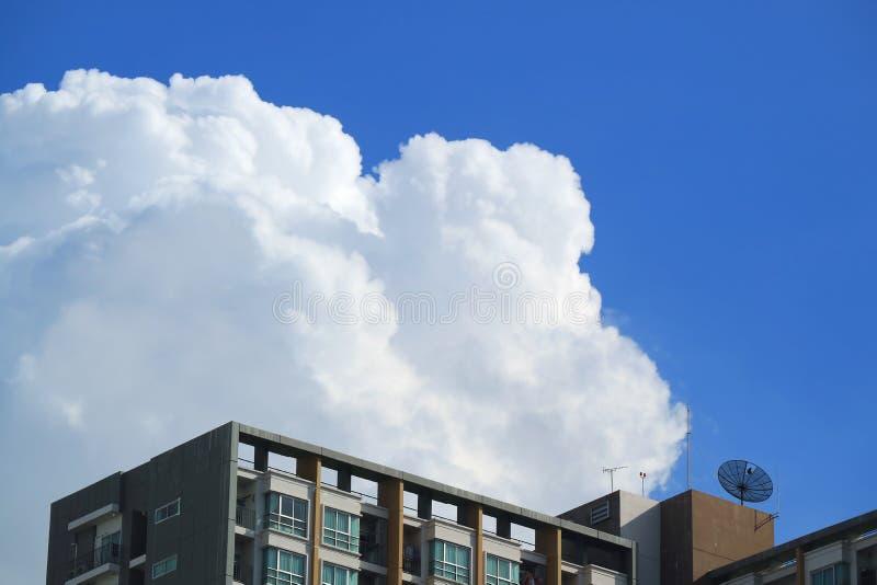 Rena vita fluffiga pösiga stackmolnmoln på livlig blå himmel över de höga byggnaderna i Bangkok arkivfoto