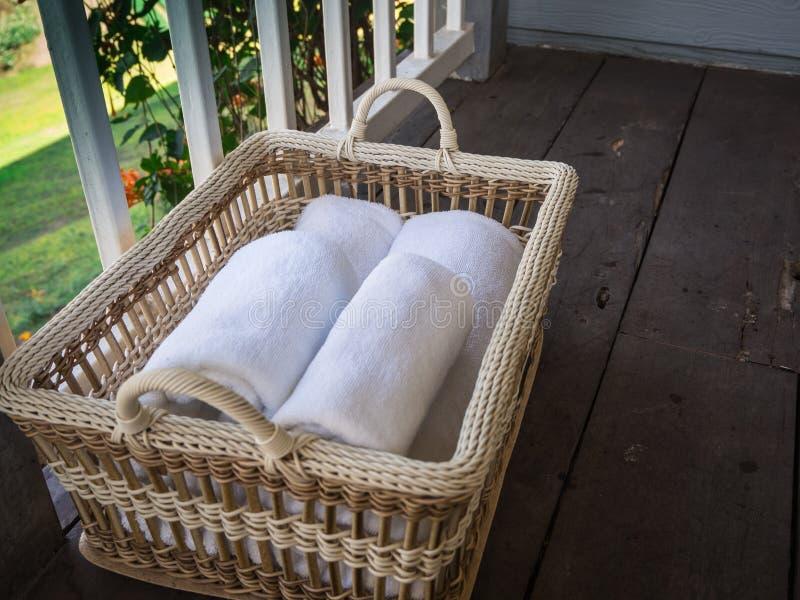 Rena vita handdukar i en korg på ett trä och en balkong fotografering för bildbyråer