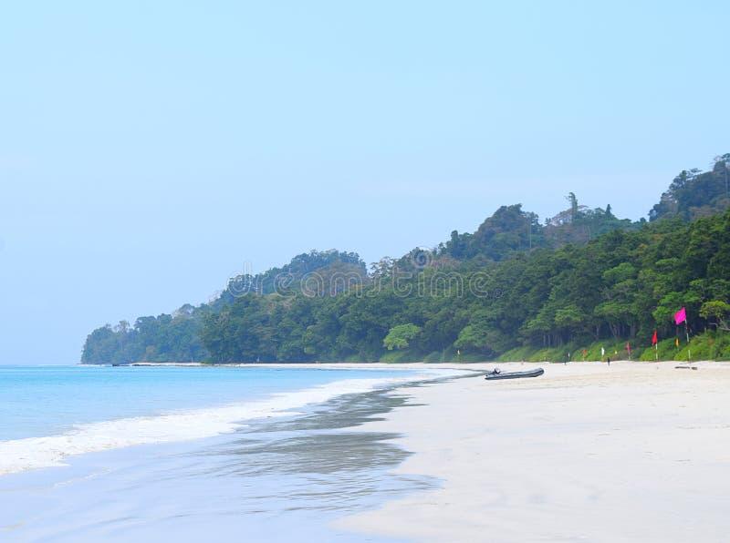Rena vita Sandy Beach, blått havsvatten, klar himmel, färgrika flaggor, fartyg och klar himmel - Radhanagar strand, Havelock ö, I royaltyfri bild
