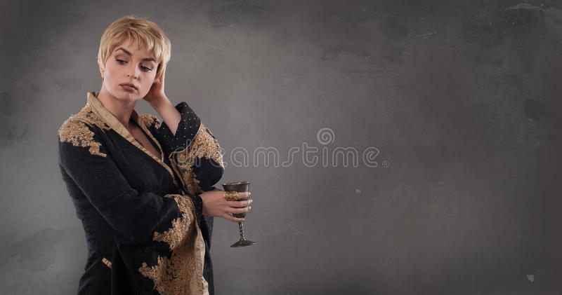 Renaissance fashion woman holding goblet with wine royalty free stock photo