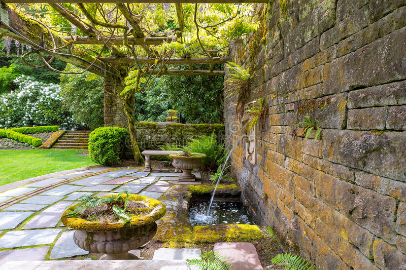 Renaissance Lion Head Water Fountain Under Wisteria Trellis stock photo