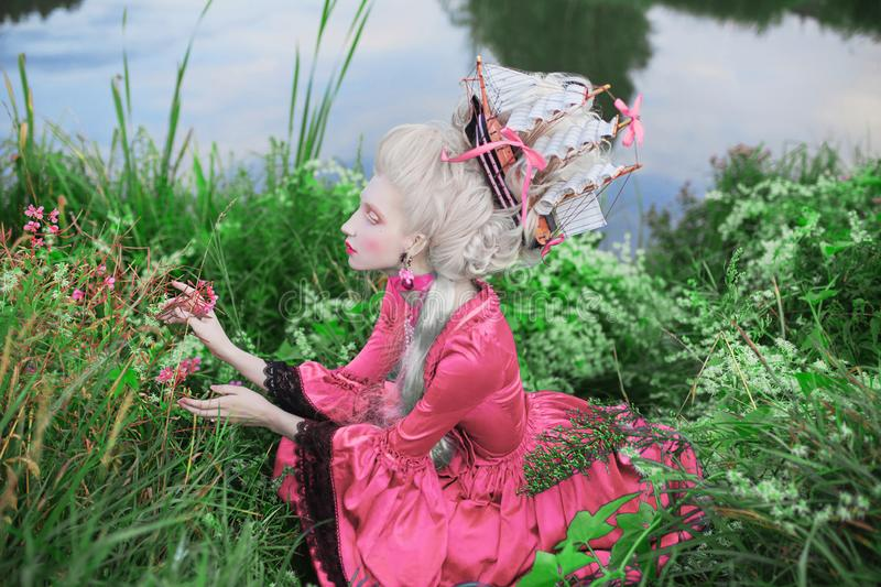 Renaissance princess with blonde hair. Fairytale rococo queen with ship in hairstyle on nature background. Rococo queen in pink royalty free stock photos