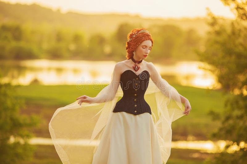 Renaissance princess on veil on nature background. Red velvet necklace. Rococo queen in corset against backdrop of sunset. Princess in veil dress. Renaissance stock images