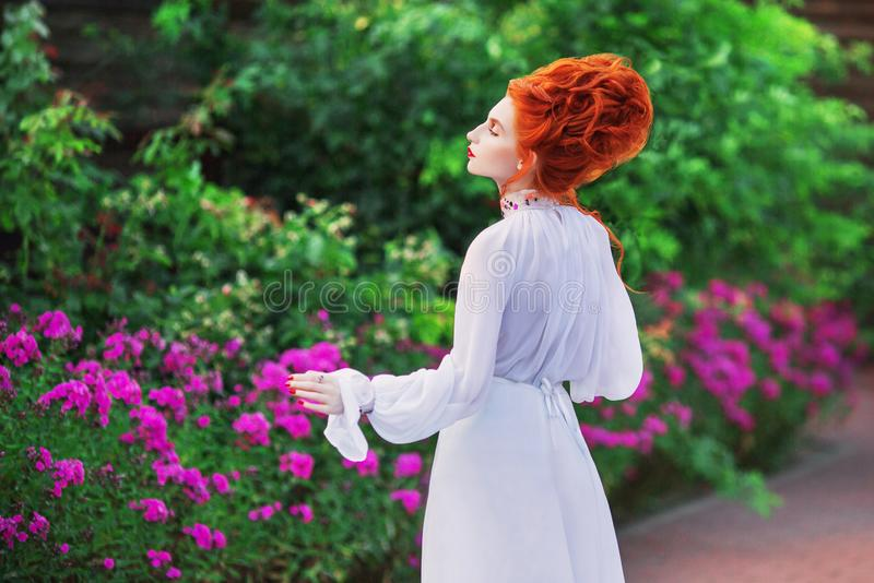 Renaissance princess in white gown. Beautiful redhead victorian girl with red hair in old white dress in park. Victorian era histo. Ric costume. White stock photo