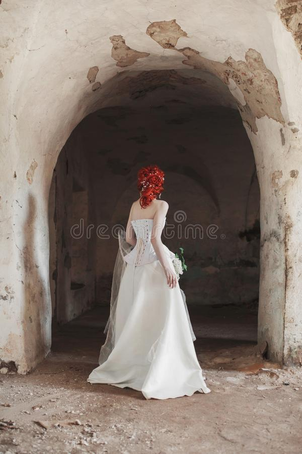 Renaissance redhead mysterious princess with hairstyle in old castle. Doll in corset. Victorian princess in palace. Fabulous mysterious phantom in white dress royalty free stock images