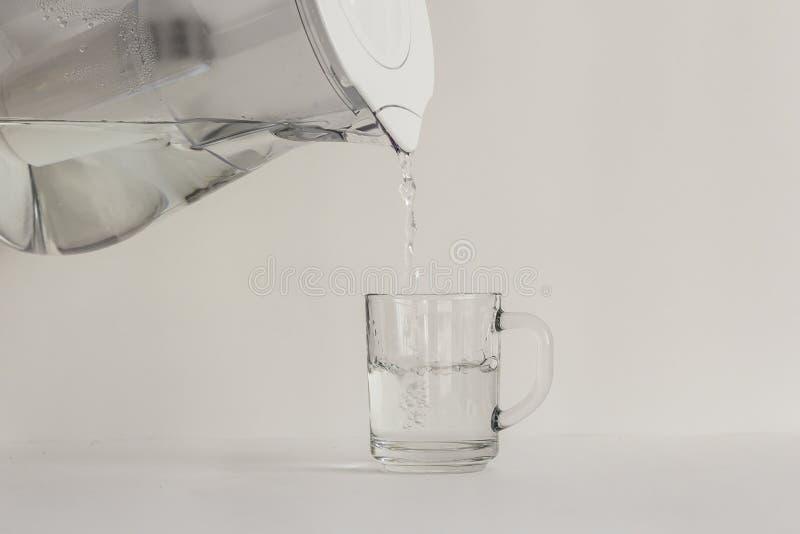 Renat vatten i en tillbringare med ett filter och ett genomskinligt exponeringsglas royaltyfri fotografi