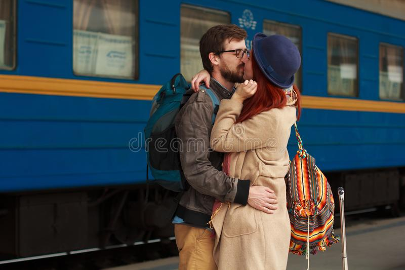 Rencontre après un voyage d'un couple heureux étreignant dans la rue dans une station de train Lumière du soleil chaude de belle  photo stock