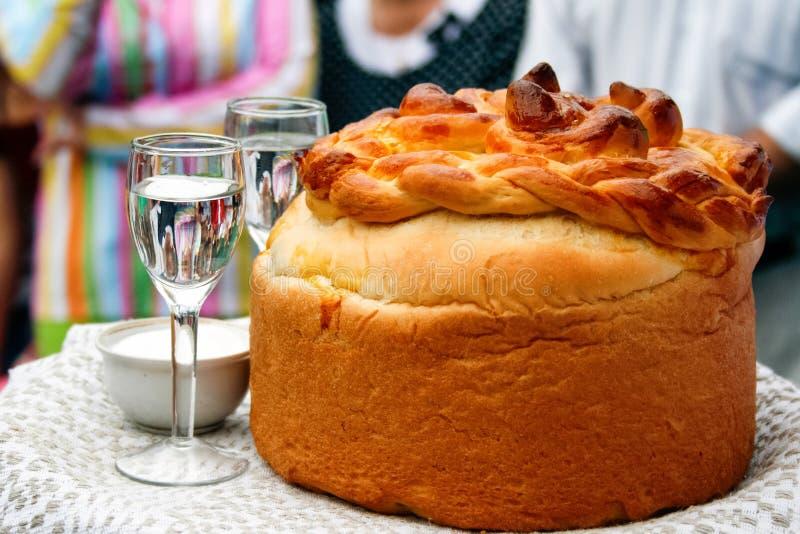 Rencontrer des nouveaux mari?s apr?s le mariage : miche de pain, sel et vodka photographie stock libre de droits