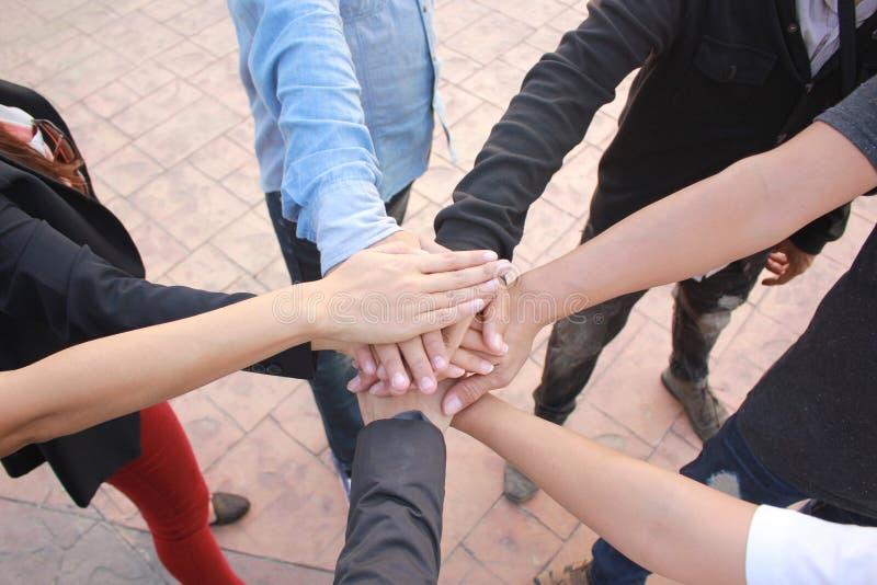 Rencontrer le concept de travail d'équipe, amitié, personnes de groupe avec la pile de mains montrant l'unité sur le fond concret photo stock
