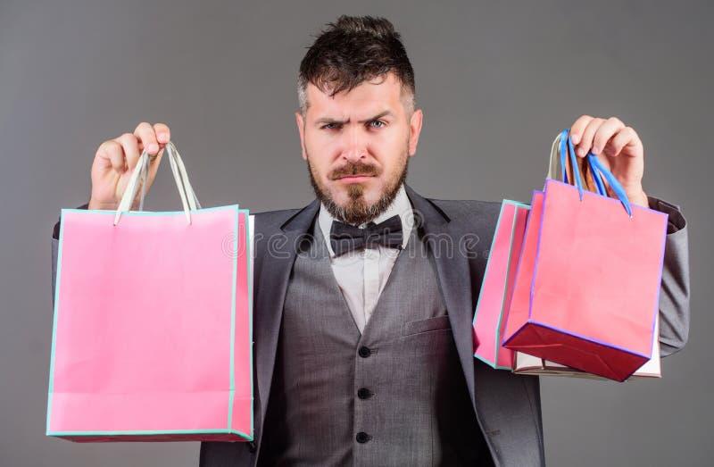 Renda comperando più allegro L'uomo d'affari elegante barbuto dell'uomo porta i sacchetti della spesa su fondo grigio Goda di di  fotografia stock