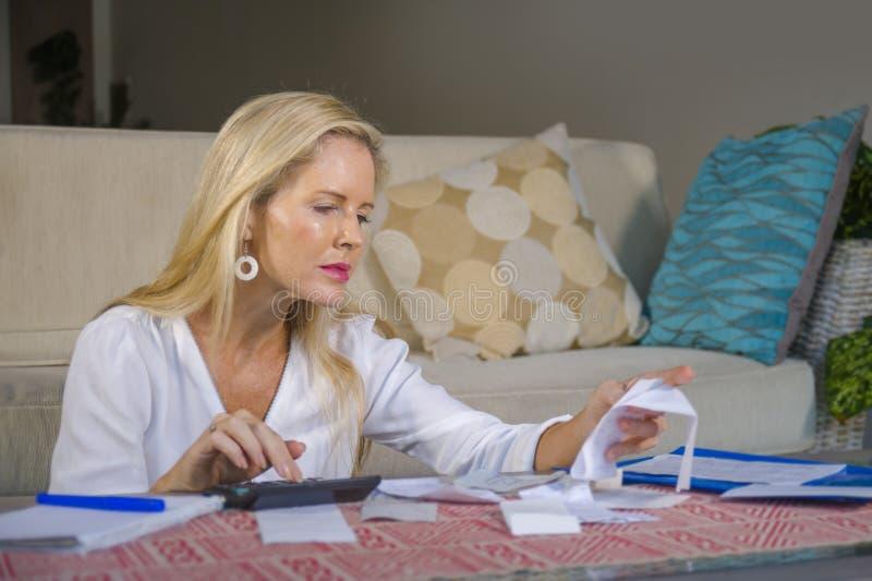 Renda de dinheiro doméstica bem sucedida calculadora relaxado da mulher 40s loura atrativa e bonita e negócio mensal financeiro b fotos de stock