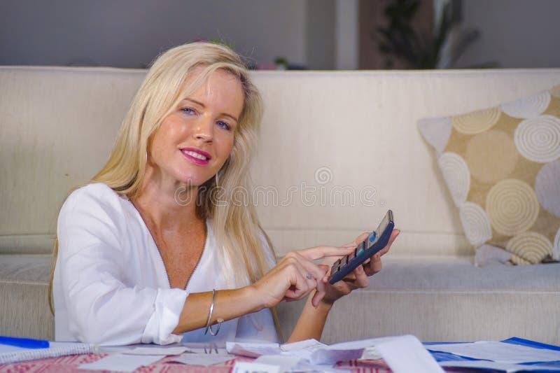 Renda de dinheiro doméstica bem sucedida calculadora relaxado de sorriso da mulher caucasiano loura feliz e bonita e busin mensal fotografia de stock