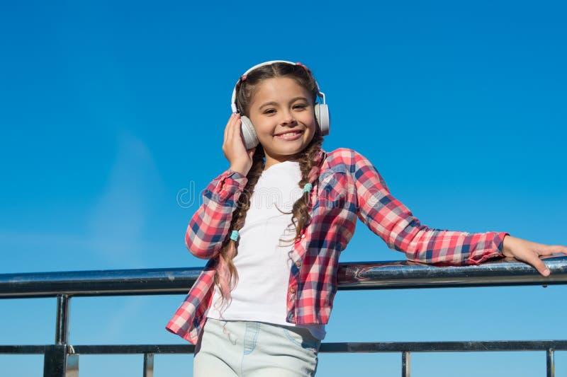 Renda il vostro bambino soddisfatto di migliori cuffie stimate dei bambini disponibili ora Il bambino della ragazza ascolta music immagini stock