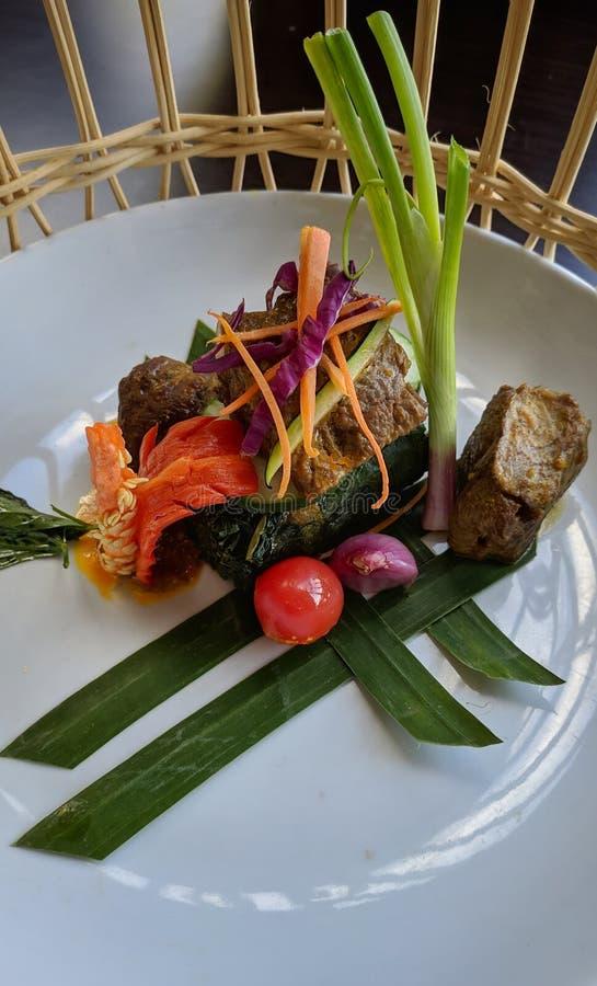 Rendang är en indonesisk kryddig kötträtt som påbörjar från det Minangkabau folket av Indonesien som tjänas som på den vita platt royaltyfria bilder
