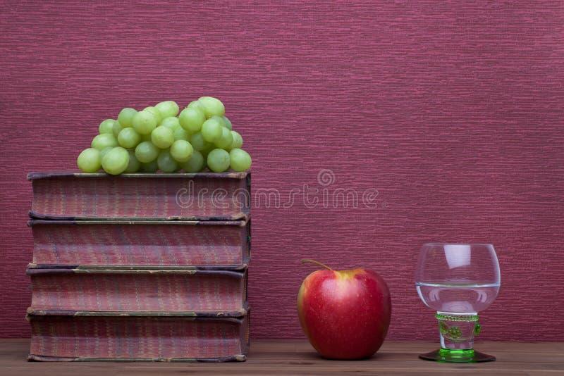 Renesans, rummer wina szkło, stare książki, jabłko i winogrona, obrazy royalty free