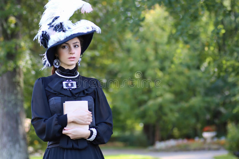 Renesansowa kobieta z książką na moscie w parku zdjęcia stock