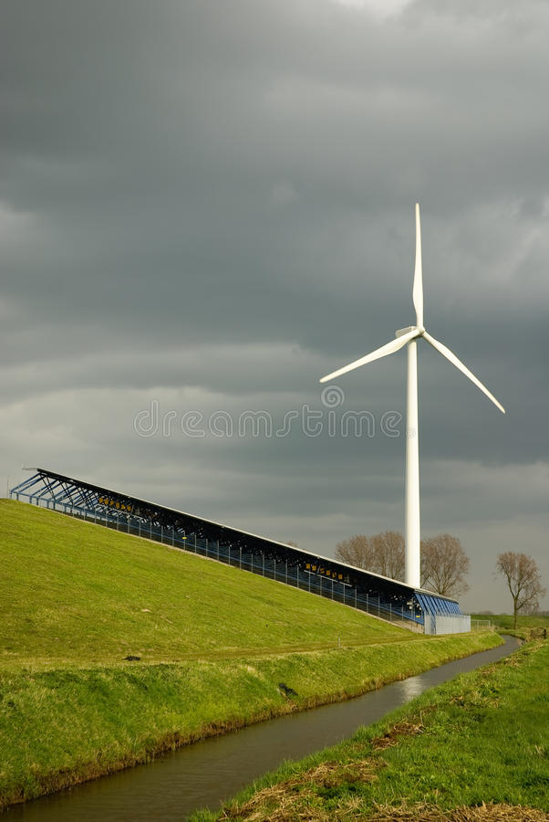 Renewable energy. Dark clouds over renewable energy sources. Wind energy and solar energy in stormy wheather royalty free stock photos