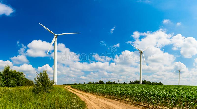 Renewable energy concept. Wind mill farm in rural area. Summer landscape stock images