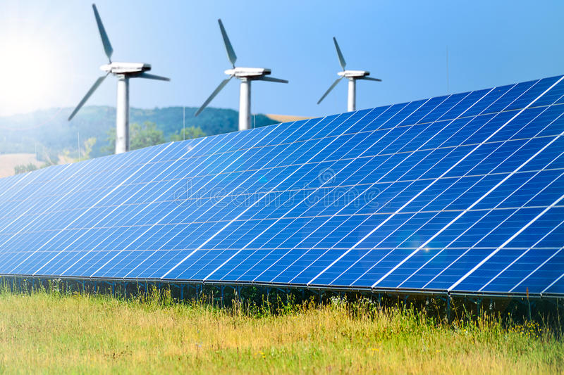 Renewable energy sources. Composite image of renewable energy sources - solar farm for photovoltaic energy and windmills for wind energy stock photos