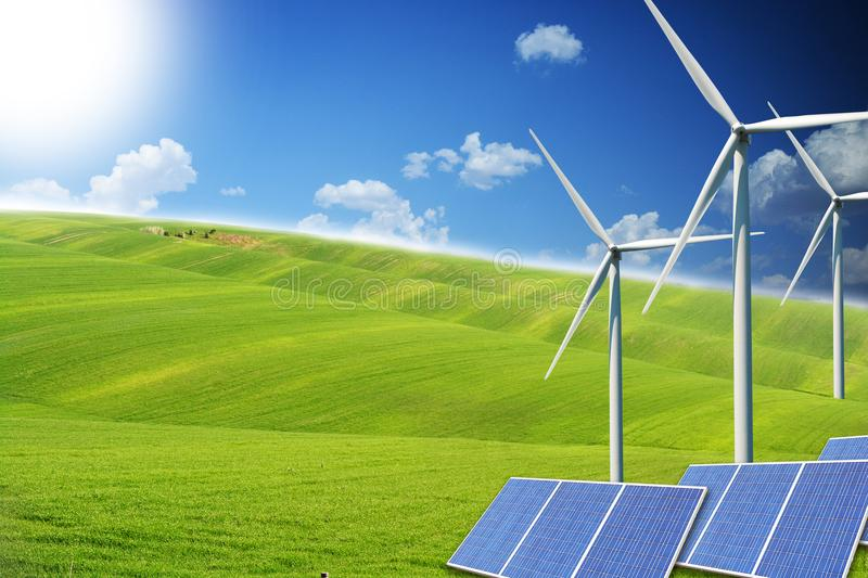 Renewable energy sources with modern solar panels and wind turbines on green field royalty free stock image