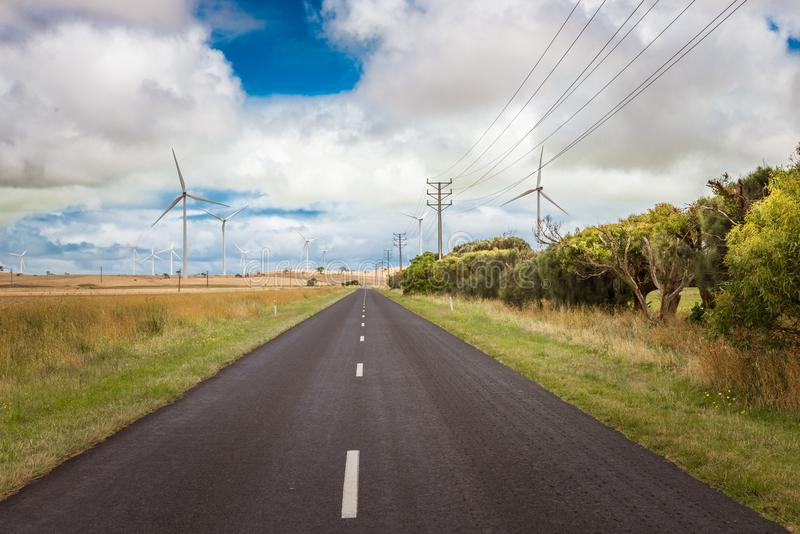 Renewable energy wind mill turbines in farm fields along the road royalty free stock images