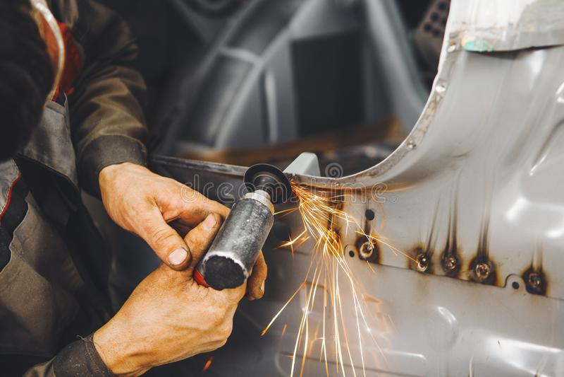 Rengöra av svetsningen Bearbeta av den svetsande pneumatiska malande maskinen för sömmar med ett slipande hjul Reparation av bilk royaltyfri bild