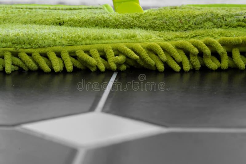 Rengörande belagt med tegel golv med ett grönt huvud för torr golvmopp arkivfoton