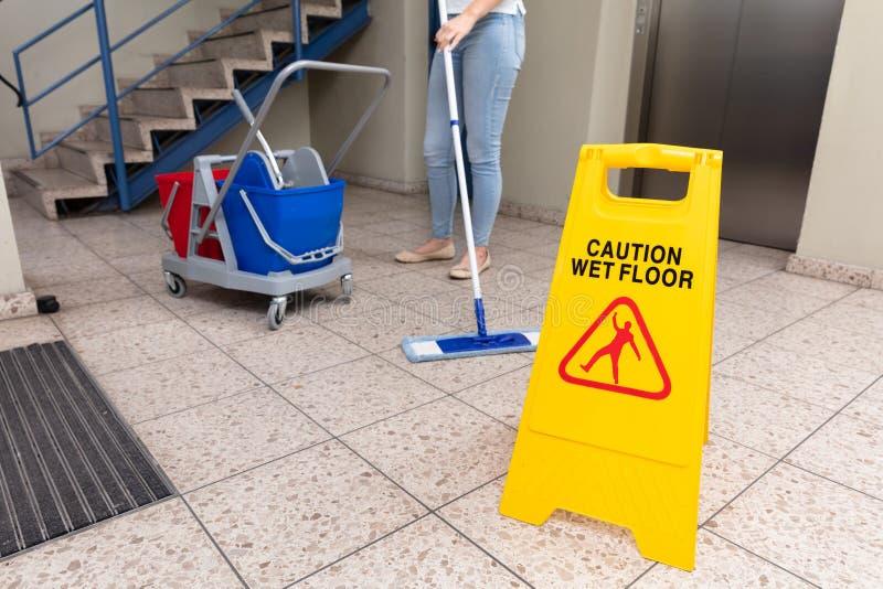 Reng?rande golv f?r kvinna med det v?ta golvvarningstecknet arkivfoto